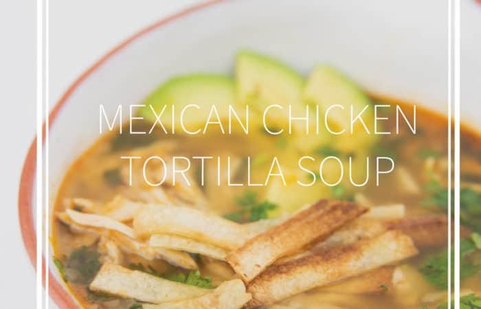 a white bowl of mexican chicken tortilla soup with avocados, tortilla stripes and cilantro