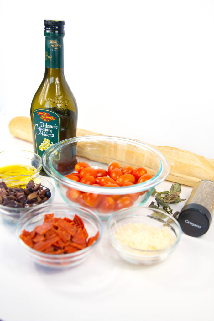 ingredients of pepperoni, parmesan cheese, olives, tomatoes, loaf of bread and seasonings