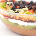 a close up of a clear bowl with layers of beans, guacamole, salsa, sour cream, lettuce, cheese, tomatoes, and olives