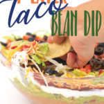 A clear bowl with layers of beans, guacamole, salsa, sour cream, lettuce, cheese, tomatoes, and olives with a chip taking a dip