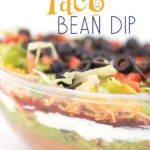 A clear bowl with layers of beans, guacamole, salsa, sour cream, lettuce, cheese, tomatoes, and olives