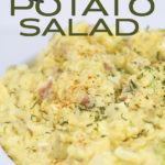 white bowl of mustard potato salad with parsley on top