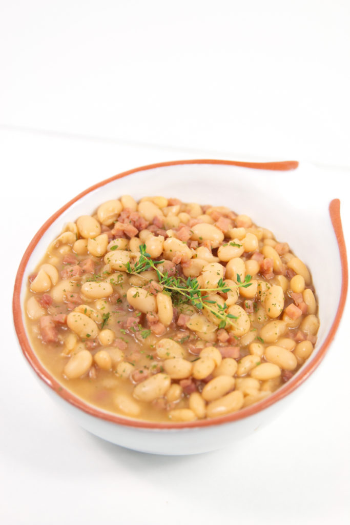 ham and bean soup in a white bowl with orange rim with thyme on top