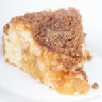 piece of apple cinnamon crumb cake with icing on top on a white plate