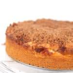 an apple cinnamon crumb cake sitting on a glass plate