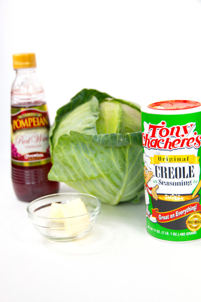 a bottle red wine vinegar bowl of butter cabbage and can of tonis cajun seasoning