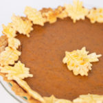 a pumpkin pie in a glass pan with leaf cut outs of crust