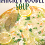 large pot of homemade chicken noddle soup with parsley, bay leaves, and sliced lemons