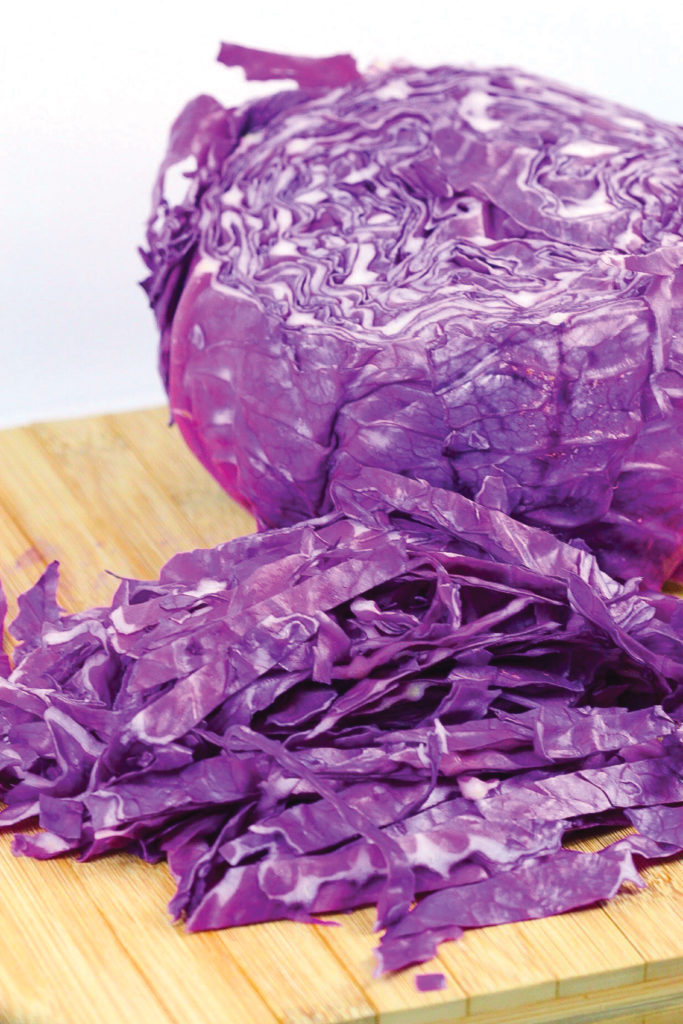 a head of red cabbage on a wood cutting board cut in half with strips of cabbage