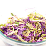 a glass bowl of green and red cabbage shredded for Mexican coleslaw