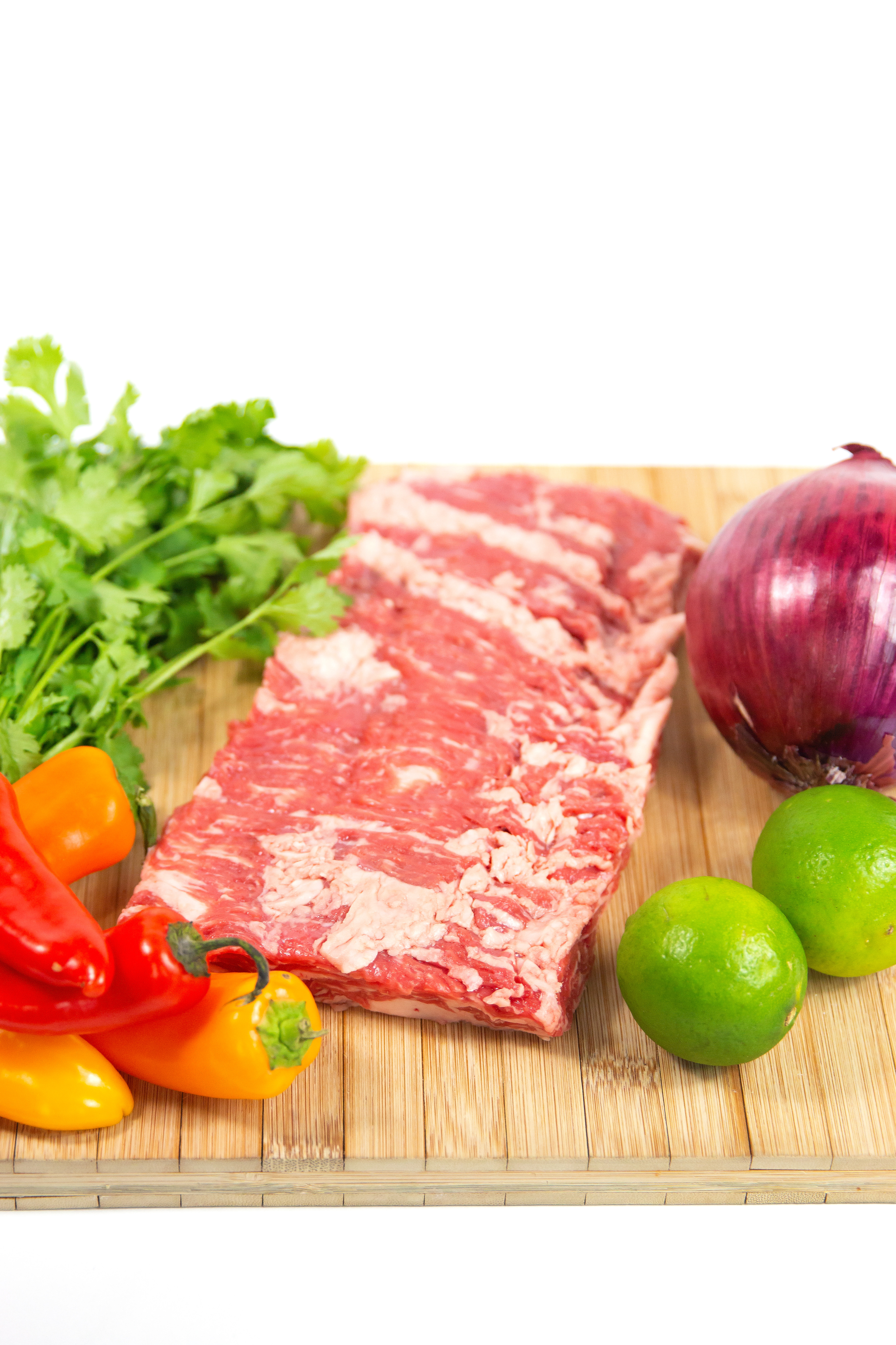 wood cutting board of raw flank steak, whole onion, peppers, cilantro, and lime