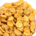 an up close shot of spicy ranch oyster crackers in a white bowl
