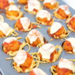 mini muffin tin of cooked spaghetti cups with popcorn chicken parmesan