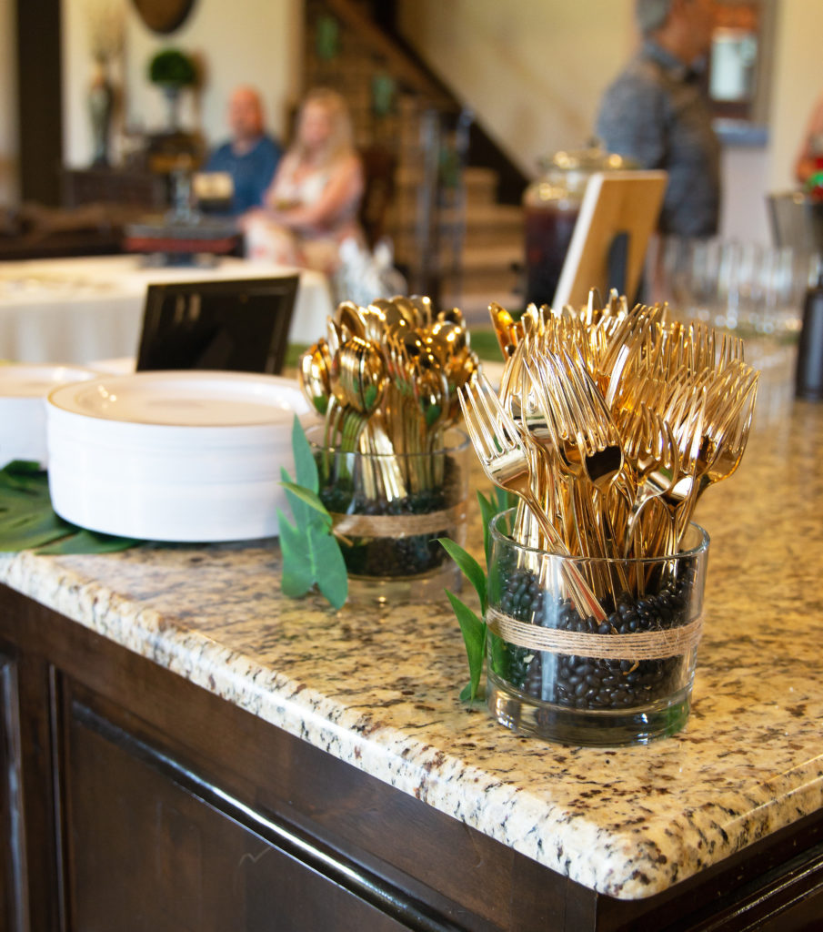 plastic plates on palm leaves with vases with gold plastic silverware on a kitchen counter