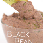 a glass bowl of black bean dip with parsley flakes on top with a green tortilla chip dipping