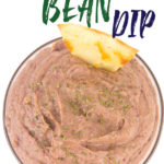 a glass bowl of black bean dip with parsley flakes on top with a tortilla chip sticking in it