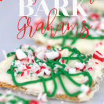 a baking pan with parchment paper with white chocolate graham crackers with green drizzle and peppermints