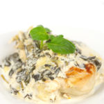 white plate of a browned chicken breast with creamy spinach and artichoke sauce with basil leaves on top