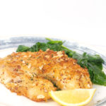 white and blue plate with almond crusted tilapia with a lemon slice and spinach
