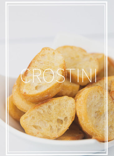 a white bowl of toasted baguette bread for easy crostini